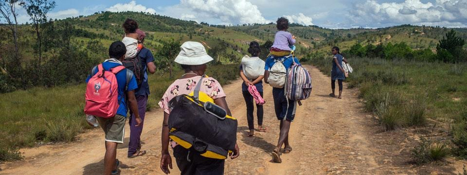 A group of adults in the hilly highlands of Madagascar, walking from the capital Antananarivo to their rural villages with luggage and children in tow. (Credit: Rijasolo / AFP)