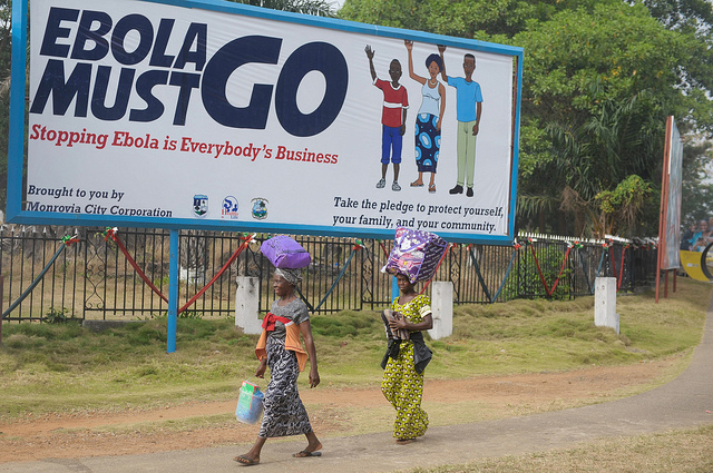 """Two women walk in front of a billboard, which says """"Ebola must go. Stopping Ebola is Everybody's Business"""" in Monrovia, Liberia."""