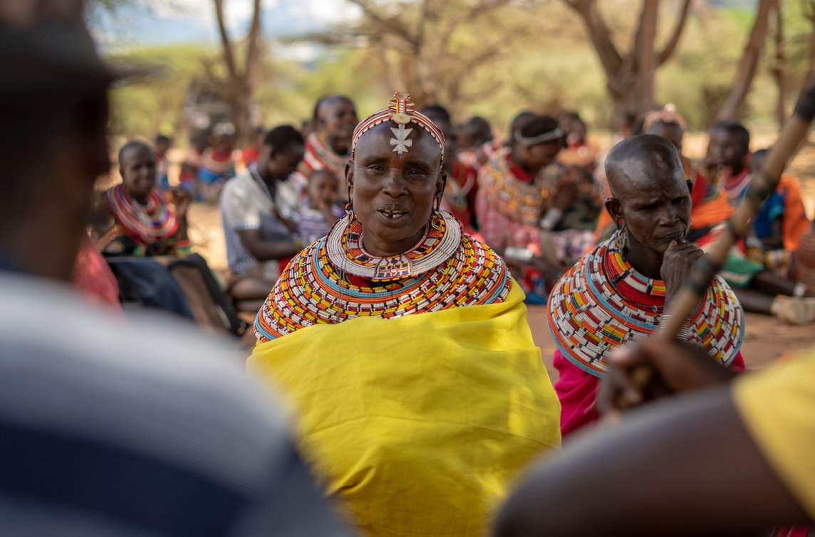 A woman speaks about land rights during a community meeting