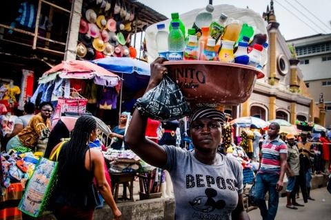 Vue d'une rue à Lagos, au Nigeria. Une marchande vend des boissons. (Photo UNSGS/ ROBIN UTRECHT)
