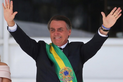 Brazil's new President Jair Bolsonaro gestures after receiving the presidential sash from outgoing President Michel Temer at the Planalto Palace, in Brasilia, Brazil January 1, 2019. REUTERS/Sergio Moraes/File Photo
