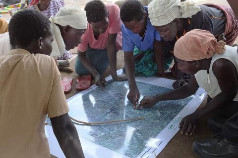 •Women in Burlobo community, Northern Uganda, use a satellite map to draw sketch maps of their land, with the help of  the Land and Equity Movement in Uganda (LEMU).
