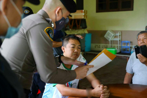 A Crime Suppression Division officer shows a document to two men wanted for false statements and embezzlement of 3,800 rai of land in Chanthaburi province. (Photo supplied)