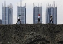 Women activists walk on top of reclaimed land during a protest against land reclamation in Jakarta Bay, Indonesia, in this April 17, 2016. REUTERS/Beawiharta/File